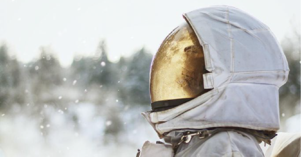 Closeup of an astronaut with a closed helmet positioned on the right half of the image, looking accoss to the left. Helmet has a gold shimmer and background is a blurred white and grey