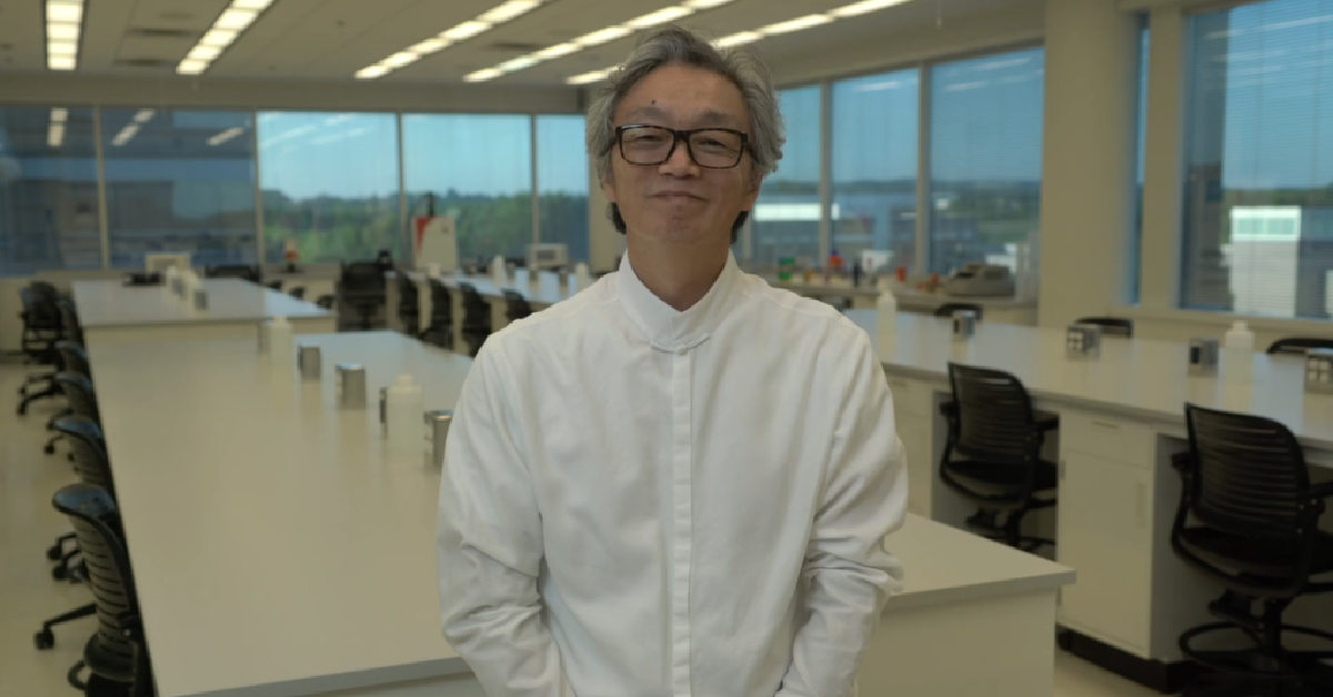 Dr. Jian Han stands facing the camera in a polished white shirt, slightly smiled. Slightly blurred for the background is the view of an empty lab room at Hudson Alpha Institute for Biotechnology